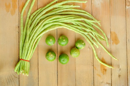 green lime and green yardlong bean on wood floor