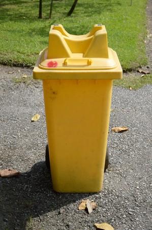 yellow plastic bin in nature garden