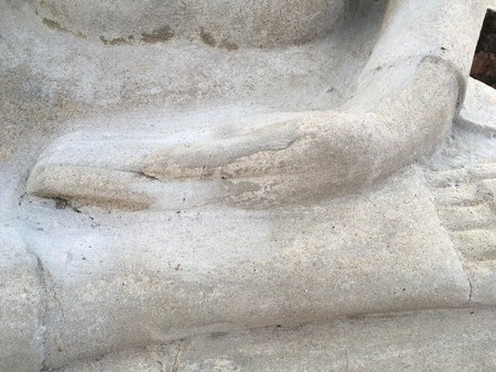close up cement hand of buddha statue in public temple at Thailand Imagens
