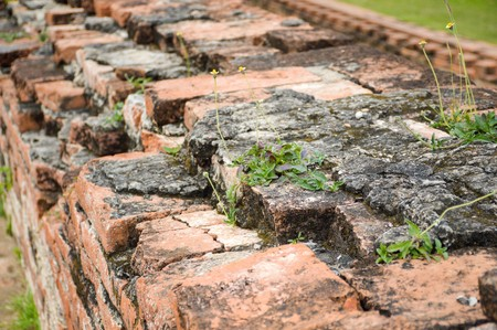 old crumbling overgrown brick wall in front of stupa at historic park thailand