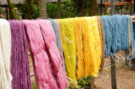 colorful raw silk thread on wood pole Stock Photo