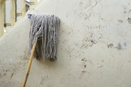old mop on cement wall
