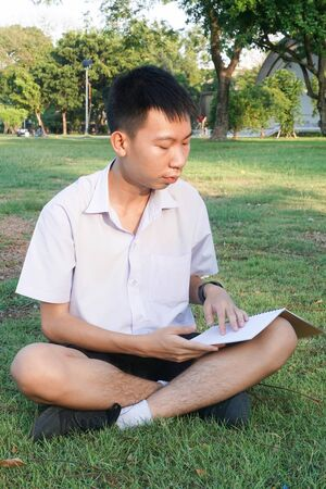 close up thai boy reading a book in nature garden Stok Fotoğraf