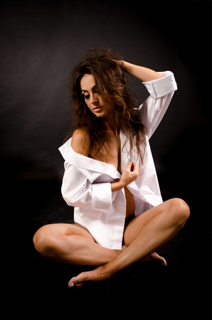 Sexy brunette woman in white mens shirt almost naked sitting on floor with black background. Valentine picture.