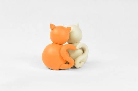 Two minimalistic animal figures in love. Lovely cat plasticine models having tails in heart shape isolated on white grey background. Happy Valentines Day in minimalism style.