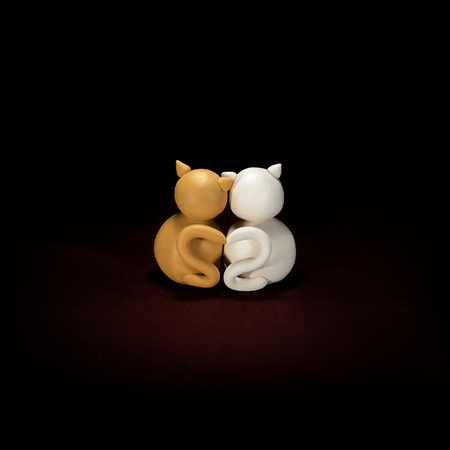 Two minimalistic animal figures in love. Lovely cat plasticine models having tails in heart shape isolated on dark red background. Happy Valentines Day in minimalism style. Stok Fotoğraf