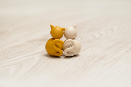 Two minimalistic animal figures in love. Lovely cat plasticine models having tails in heart shape. Concept for Happy Valentines Day.