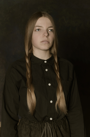 Portrait of woman with blonde braids in clothes style of thirties. Ukraine. Deep angry look, sad eyes.