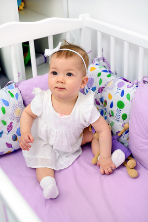 Portrait of 7 month old baby girl sitting in white crib in light room