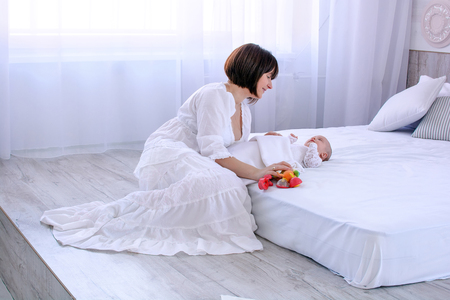 Mother playing with baby with toys in light white bedroom. Woman lovely looking at her newborn Stok Fotoğraf