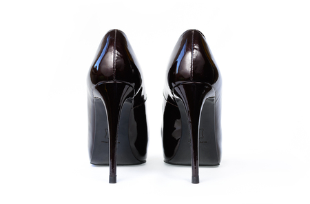 Lacquered black sexy shoes with high heels isolated on white. Women classic varnished shoes from back view close up. Pair of fashionable elegant luxury footwear.