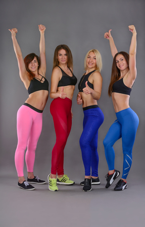 Sport girls stand together in colorful sportwear. Group of women with slim bodies, tight hips and sexy butts with fit shapes. Fitness success and thumb up. Firm buttocks. Healthy lifestyle.