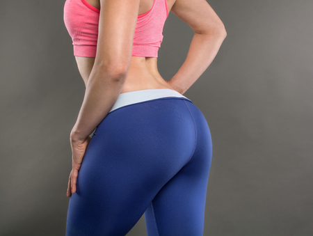 Closeup of fitness woman with fit cheeks, tight hips and firm buttocks in workout leggins. Perfect female ass in shape of sexy bottom and big butt. Slim girl body isolated on white background. Foto de archivo