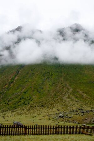 rock shrouded in fog, covered with green grass, a wooden fence under the mountain Stockfoto - 133475777