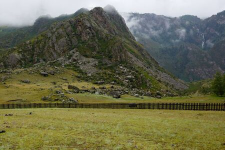 rock shrouded in fog, covered with green grass, a wooden fence under the mountain