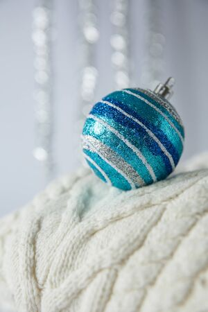 Christmas. Christmas toy silver, blue striped ball with sparkles on a white knitted woolen sweater. Stock Photo