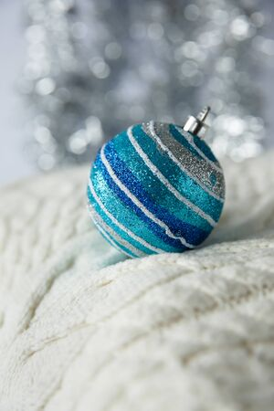 Christmas. Christmas toy silver, blue striped ball with sparkles on a white knitted woolen sweater. 写真素材