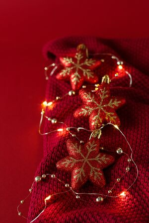 Christmas red background with red Christmas toys, beads and a garland on a burgundy knitted fabric.
