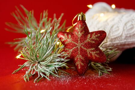 Red Christmas toy and fir branch in the snow, against the background of a knitted white sweater and garland