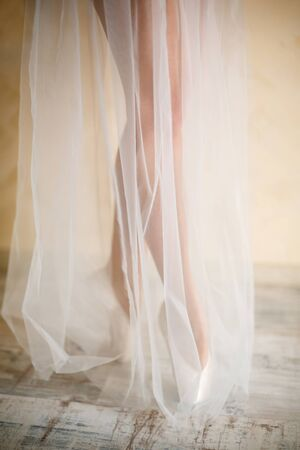 ballerina in a white dress made of light fabric, legs on pointe shoes
