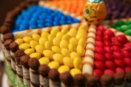 Cake decorated with colored dragees, chocolate wafer rolls and candy