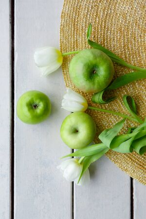 green apples and white tulips lie on a straw hat and on a white background from wooden boards