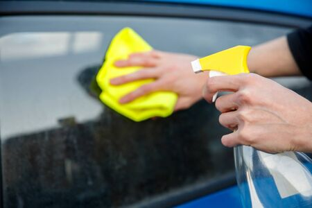 man with a spray bottle and a yellow rag in his hand wipes the dirty glass of a car window