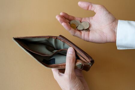 Empty wallet in the hands of a man on a light solid background, top view. Bankruptcy and insolvency in the economy and finance. Standard-Bild