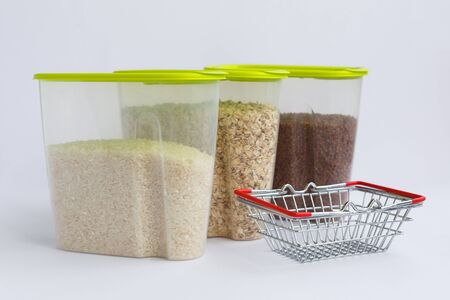 various groats in containers or jars on a white background and a small grocery basket. Rice, oatmeal and buckwheat