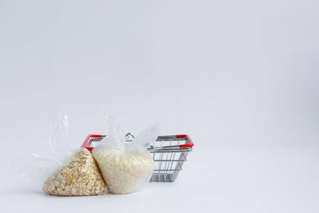 various groats in packages near the grocery basket on a white background. Rice and oatmeal
