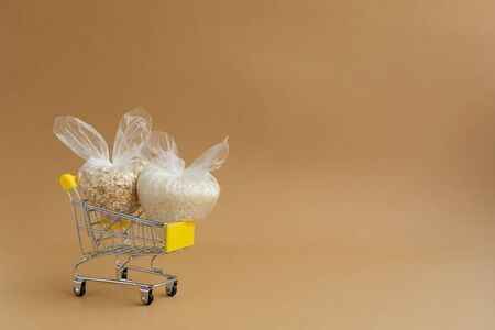 various groats in packages in a grocery cart on a brown background. Rice and oatmeal Stockfoto