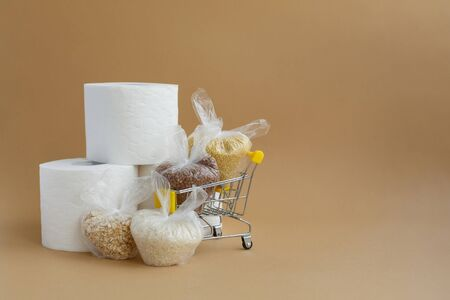toilet paper and various cereals in small plastic bags in a grocery cart on a brown background. Rice and oatmeal, buckwheat and millet Stockfoto