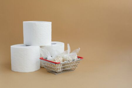 toilet paper and various cereals in small plastic bags in a grocery basket on a brown background. Rice and oatmeal Stockfoto
