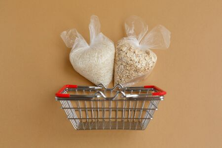 various groats in packages in a grocery basket on a brown background. Rice and oatmeal Stockfoto