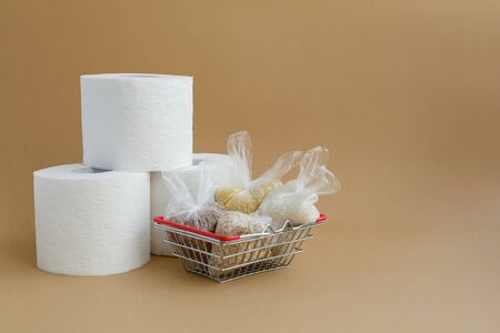 toilet paper and various cereals in small plastic bags in a grocery basket on a brown background. Rice and oatmeal, buckwheat and millet