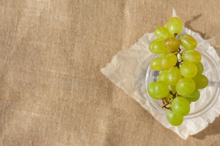 Flat lay, still life and food photo. A dish with a bunch of berries of green grapes stands on a burlap
