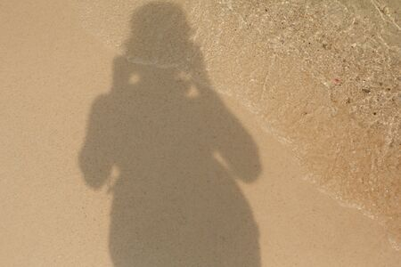 Shadow of a man on the sandy shore of a sea beach in the waves of water. Natural background.