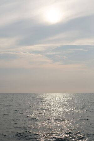 Natural background. The sun goes down to the horizon above the sea or ocean. Sunset over the water.