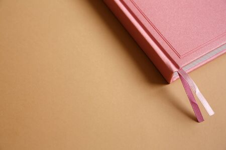 Cover of pink notebook, diary or book on brown paper background