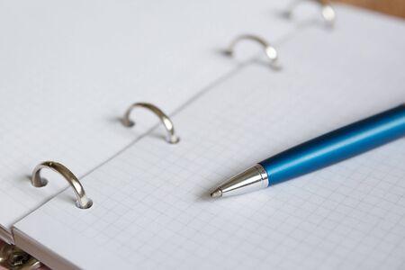 A blue pen lies on a white sheet of a notebook. Open squared school notebook