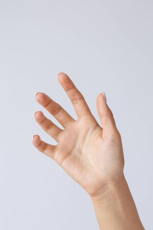Gesture and symbol. Female hand holds or shows a smartphone. Hand for advertising smartphones