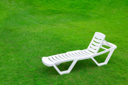 Recreation and tourism advertising. Empty white plastic chair or chaise longue, on the green grass of a fresh lawn. Place for text 写真素材