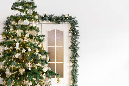 Congratulatory new year card. Christmas tree decorated with a garland, on the background of the door. Place for text.