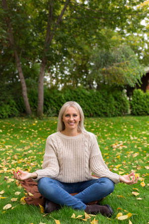 lawn is covered with yellow autumn leaves. Woman sitting cross legged in lotus position and meditating, on green grass. Reklamní fotografie
