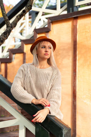 Young beautiful blonde woman in sweater and fedora felt hat, stands against yellow wall. Copy space and place for text Zdjęcie Seryjne