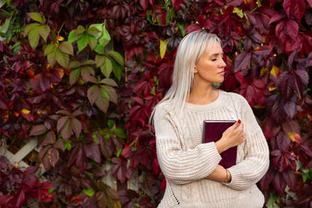 Young beautiful woman in sweater, stands with book in her hands near vine with red autumn leaves. Student holds textbook in her hand. Copy space and place for text.