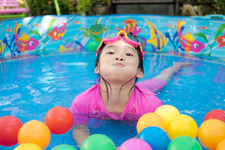 kiddie: A baby girl in pink suit playing water and balls in blue kiddie pool