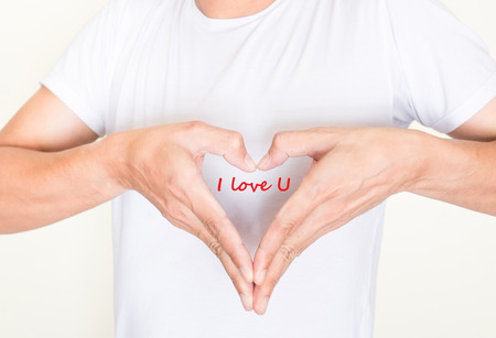 i love u: heart shape hands on left side chest of a man in white shirt. Words I love U in the center of the heart