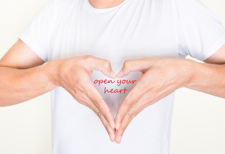 open your heart: heart shape hands on left side chest of a man in white shirt with words  open your heart