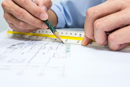 鉛筆と定規を使用して図面に距離を測定しているエンジニア